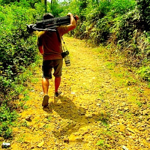 Sambil membawa tripod di pundaknya, mas Popo harus melewati jalanan berbatu di tengah teriknya matahari. (Foto: Yudha PS)