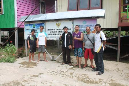 Berfoto bersama Kepala Desa Ubol Alung, Muriono (berjaket hitam).