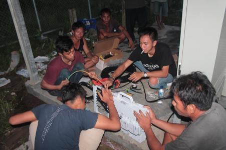 Para teknisi tengah mempersiapkan menara telepon seluler di Ubol Alung. (Foto: Yudha PS)