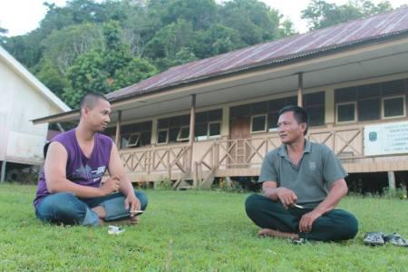 Okeu, kawan saya, berdiskusi dengan Sekretaris Desa Ubol Alung sembari menikmati sore. (Foto: Yudha PS)